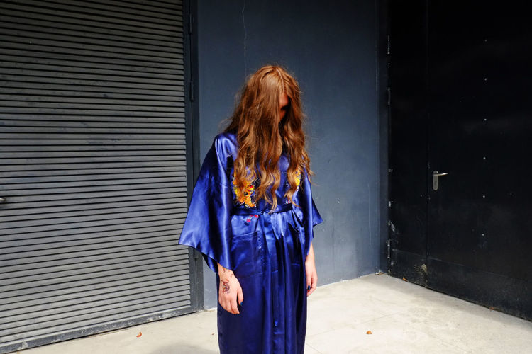 Spooky woman wearing blue robe while standing against wall