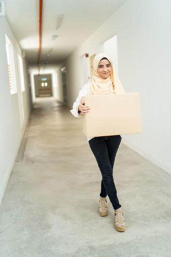 Woman holding cardboard box while standing in corridor