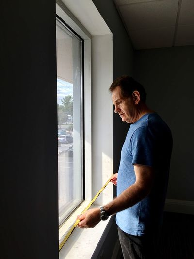 Side view of man measuring window with tape measure at home