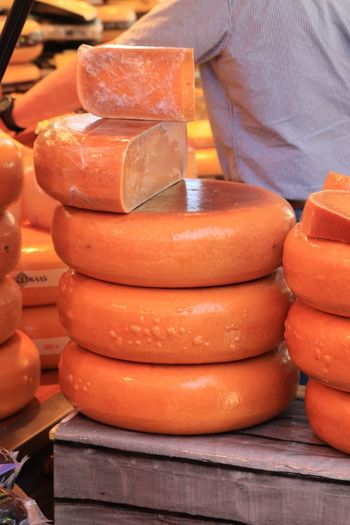 Cheese for sale in street market Cheese Wheels Food Stack Food And Drink For Sale Market Freshness Retail  Large Group Of Objects Orange Color Healthy Eating Brown Focus On Foreground Business Day Wellbeing Close-up Market Stall