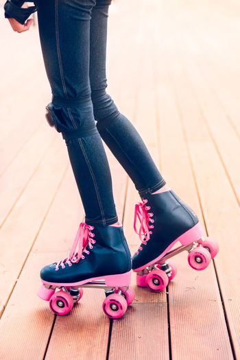 Low Section Of Teenage Girl Roller Skating On Boardwalk