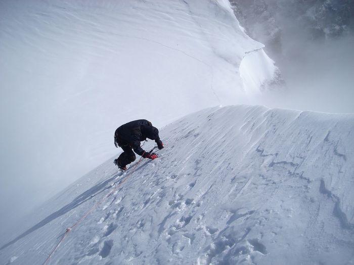 Man climbing snow covered mountain