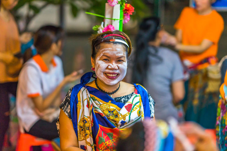 Portrait of smiling woman in costume wearing facial mask