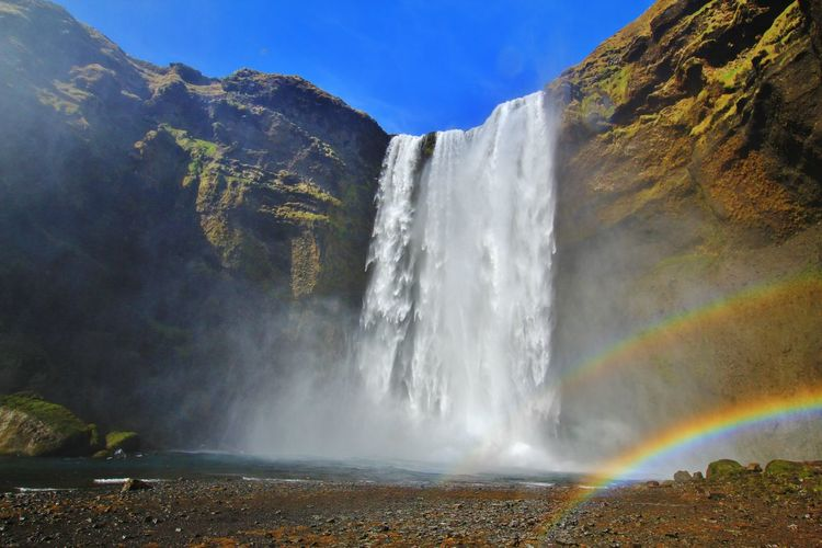 Scenic view of waterfall and rainbow against sky