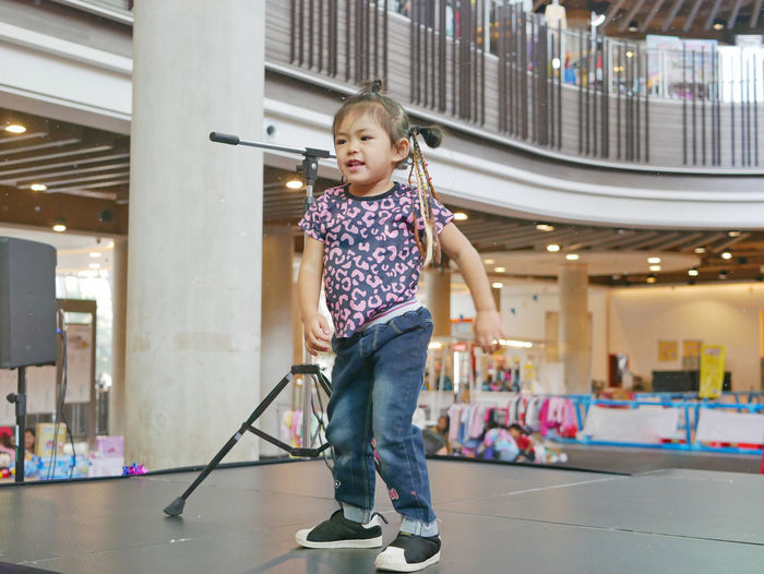 Full length of cute girl standing in building