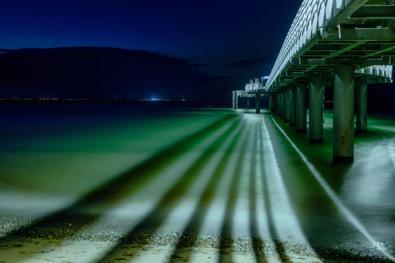 Light trails of an illuminated pier on the water at night