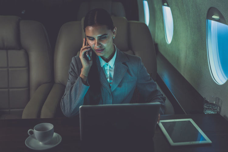 Businesswoman talking on mobile phone while using laptop in airplane