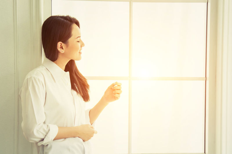 Young woman standing by window
