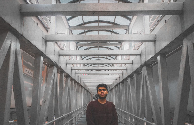 Portrait of young man standing on covered bridge