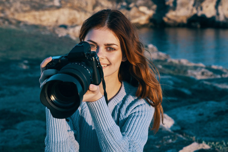 Portrait of woman photographing water