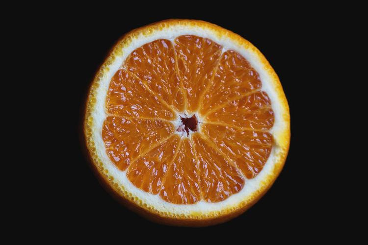 Close-up of orange slices over black background