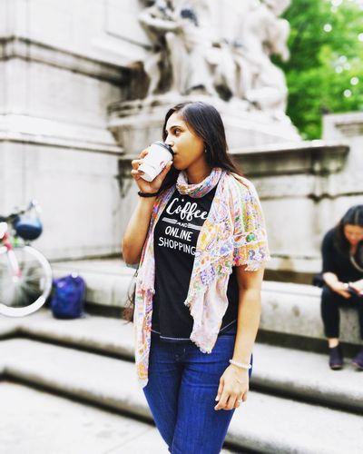 Woman Looking Away While Drinking Coffee In City