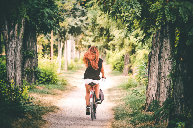 Redhead on a bicycle Tree Plant Transportation Real People Lifestyles Bicycle Casual Clothing Hairstyle Leisure Activity One Person Tree Trunk Trunk Nature Hair Rear View Riding Ride Long Hair Women Land Outdoors Redhead Girl Spontaneous Inspiration