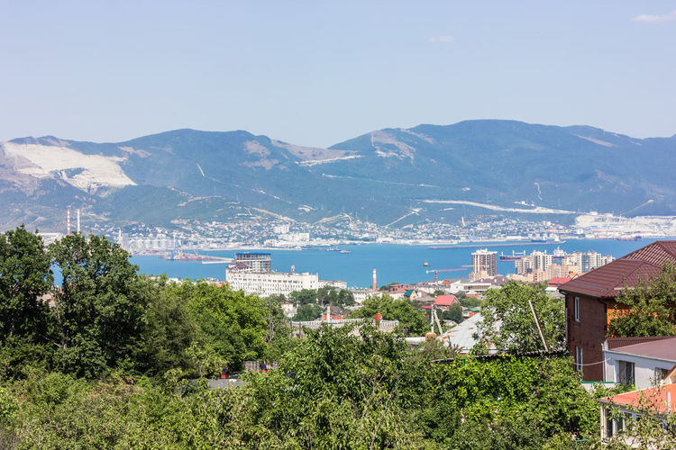 City landscape. On the photo there are mountains, sea and city buildings. Novorossiysk in the summer on a clear sunny day. Architecture Beauty In Nature Building Building Exterior Built Structure City Day Environment Habbit High Angle View House Mountain Mountain Range Mountains Nature No People Outdoors Plant Residential District Scenics Scenics - Nature Sky TOWNSCAPE Tree Water