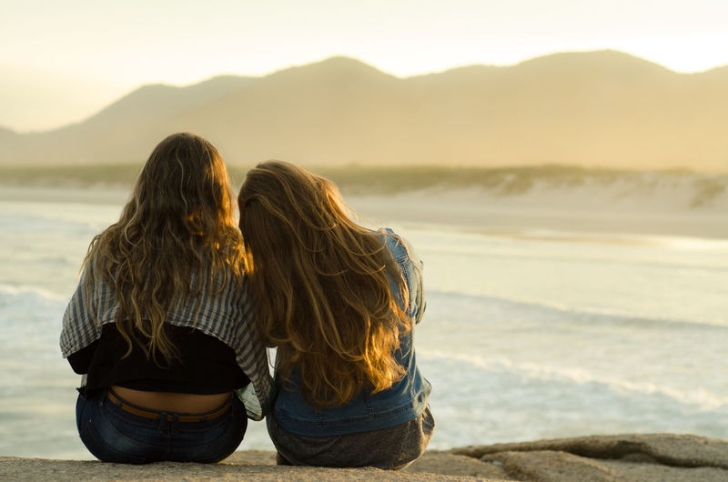 Beauty In Nature Casual Clothing Focus On Foreground Leisure Activity Lifestyles Looking At View Mountain Nature Outdoors Rear View Relaxation Sea Shore Sunset Tourism Tourist Tranquil Scene Tranquility Vacations Water The Following