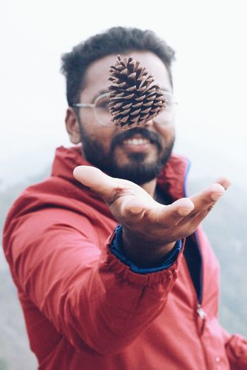 Close-Up Of Young Man Throwing Pine Cone Into The Air