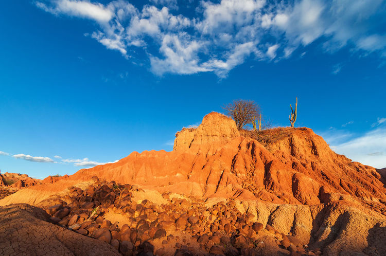 Red hill in a desert with large rocks scattered around the base in Huila, Colombia Arid Climate Beauty In Nature Cactus Clouds Colombia Desert Drought Heat Hot Huila  Landscape Nature Neiva Pillar Rock Sand Scenery Scenics Stone Tatacoa Tourism Tranquil Scene Valley View Wilderness