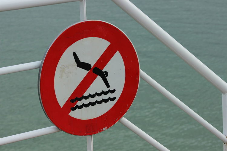No diving sign on railing against sea