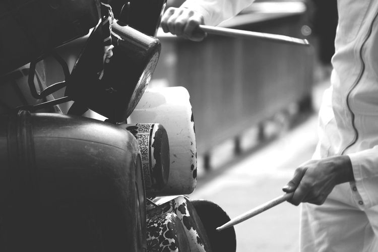 Midsection of street musician playing music from cooking utensils