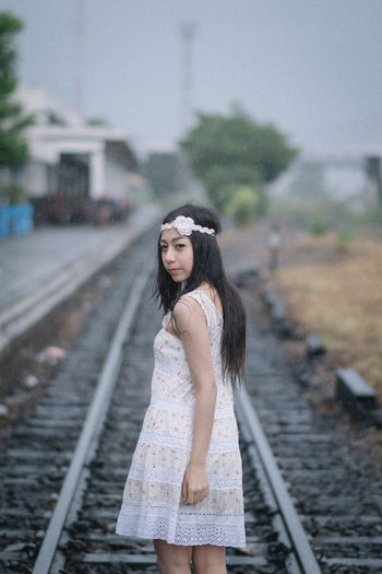 Portrait of woman standing on railroad track