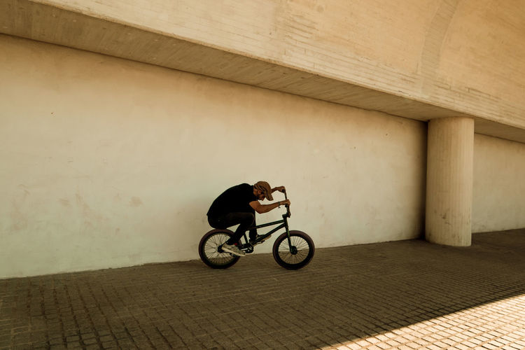 Side view of man riding bicycle against wall