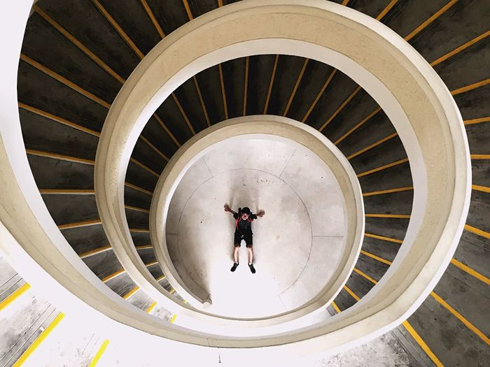 High Angle View Of Man At Bottom Of Spiral Staircase
