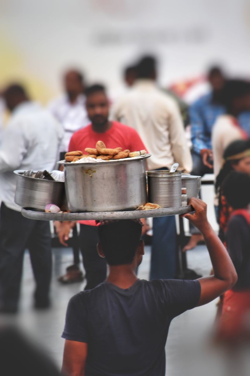 men, group of people, real people, focus on foreground, food and drink, food, people, occupation, rear view, incidental people, casual clothing, business, crowd, standing, lifestyles, day, group, adult, market, uniform, street food