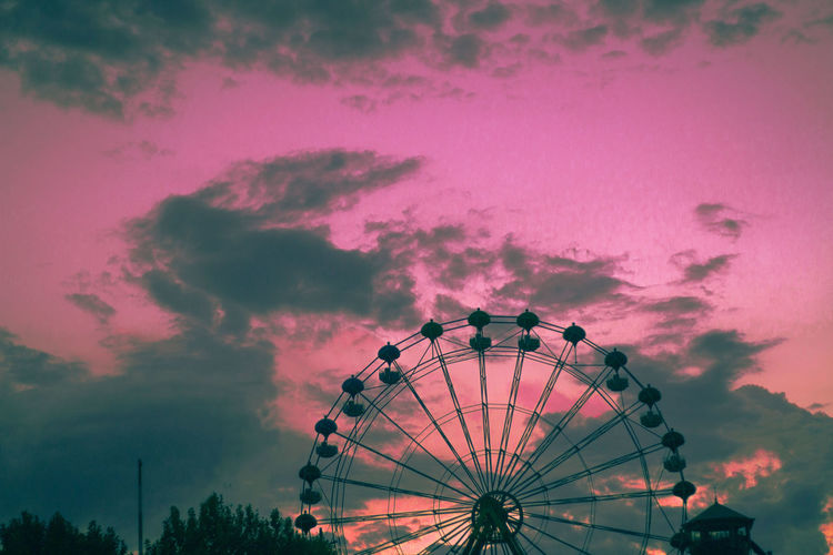 Low angle view of ferris wheel against sky at sunset