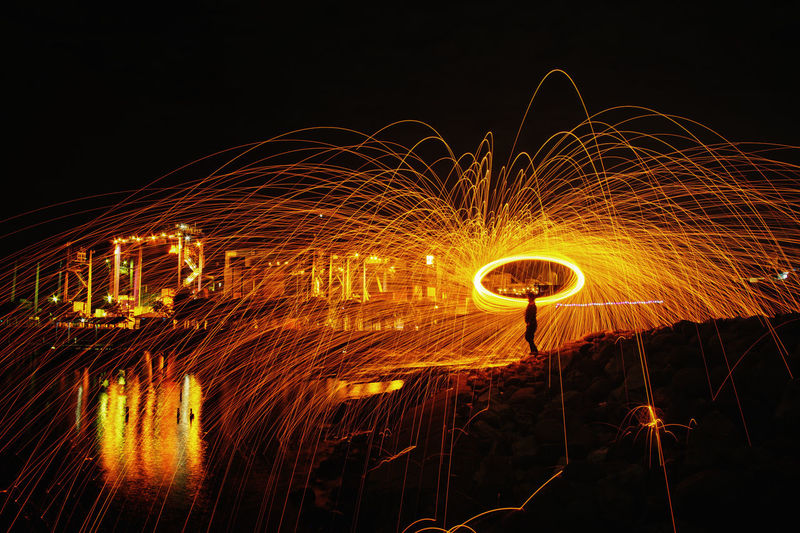 Person Standing With Wire Wool Against Sky At Night
