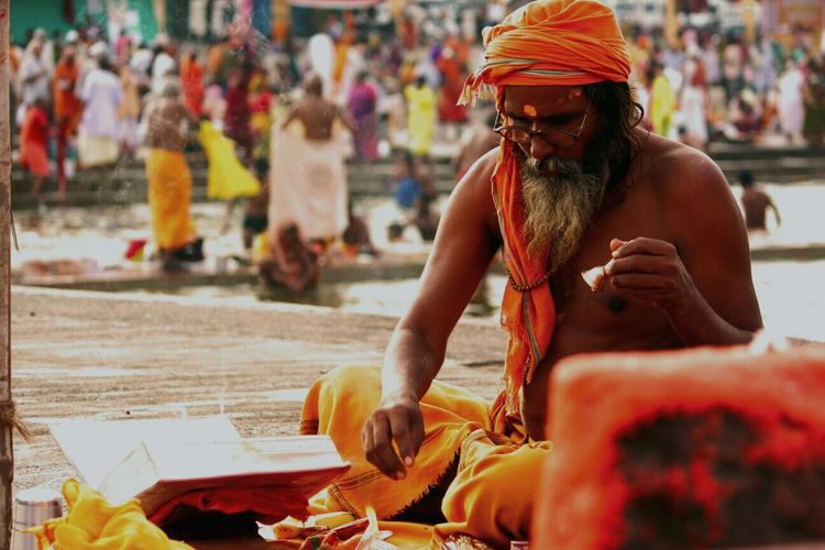 Shirtless sadhu praying at riverbank during kumbh mela
