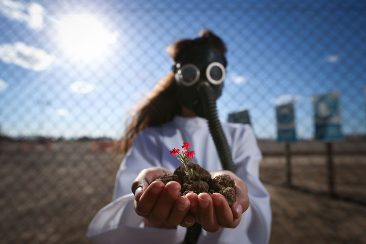 Girl Wearing Gas Mask While Holding Flower Plant