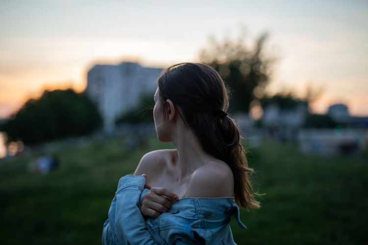 Woman wearing denim jacket standing against sky during sunset