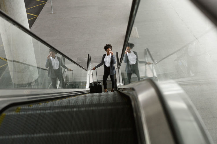 High Angle View Of Businesswoman Standing On Escalator At Airport