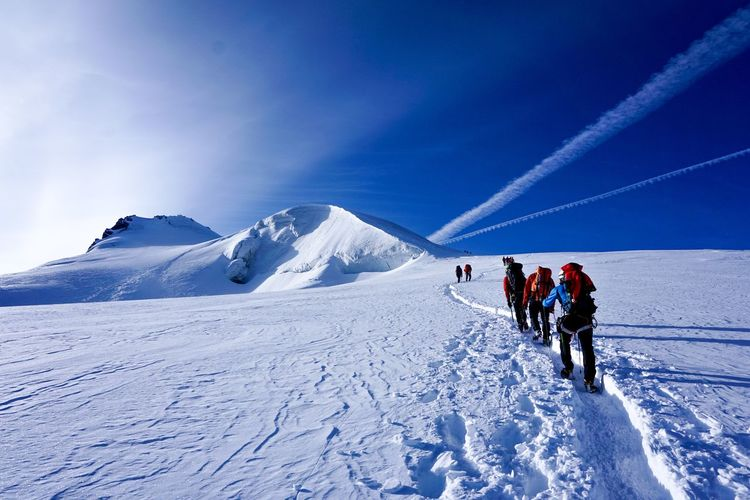 People hiking on snow covered land against sky