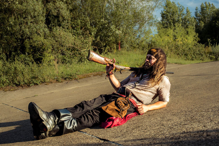 Side view of young woman lying on road against trees