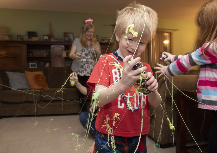 A five-year-old boy celebrates New Year's Eve at his home while spraying silly string with his family. Childhood Child Real People Girls Women Lifestyles Leisure Activity Females Indoors  Family Holding Bonding Togetherness Two People Sister Innocence Daughter Silly String Celebration New Years Eve New Years Eve 2019 Party Fun New Year's Eve
