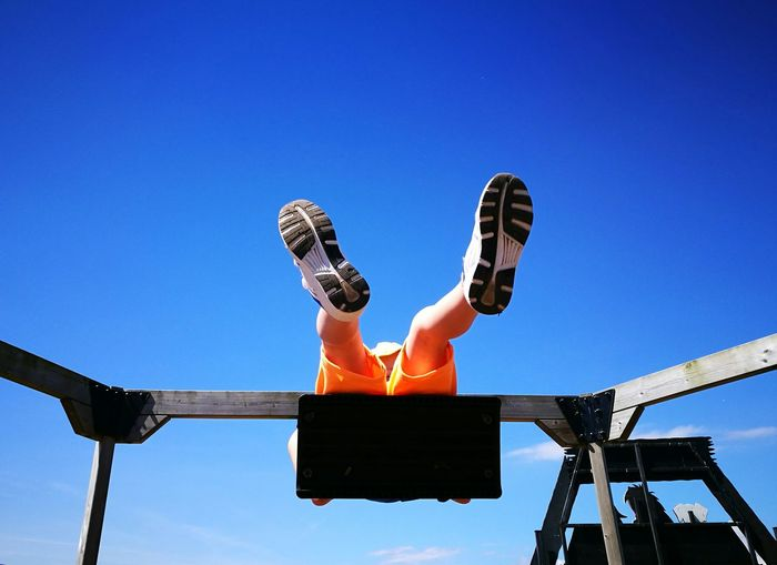 Low angle view of boy swinging against blue sky