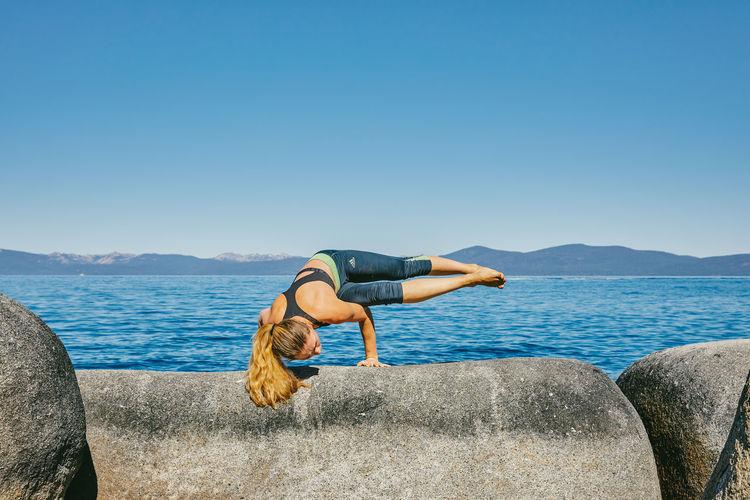Woman on rock against sea against clear blue sky