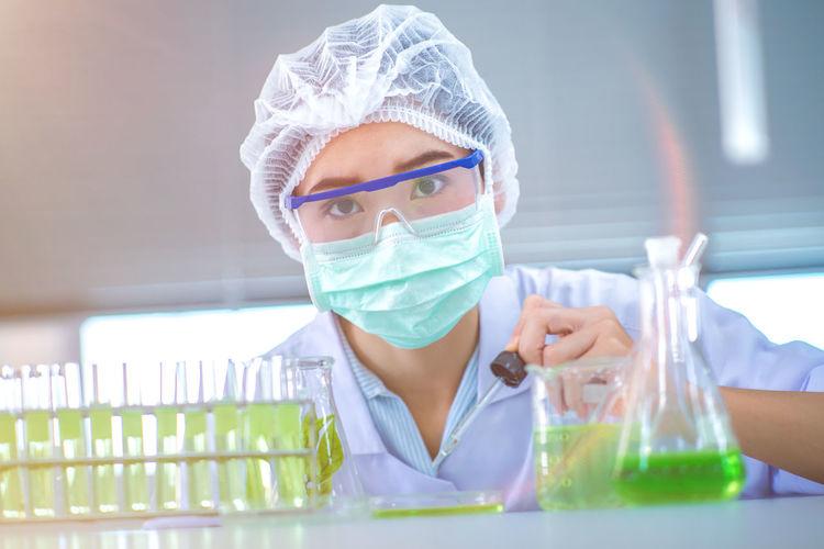 Portrait Of Scientist Adding Sample To Petri Dish With Pipette
