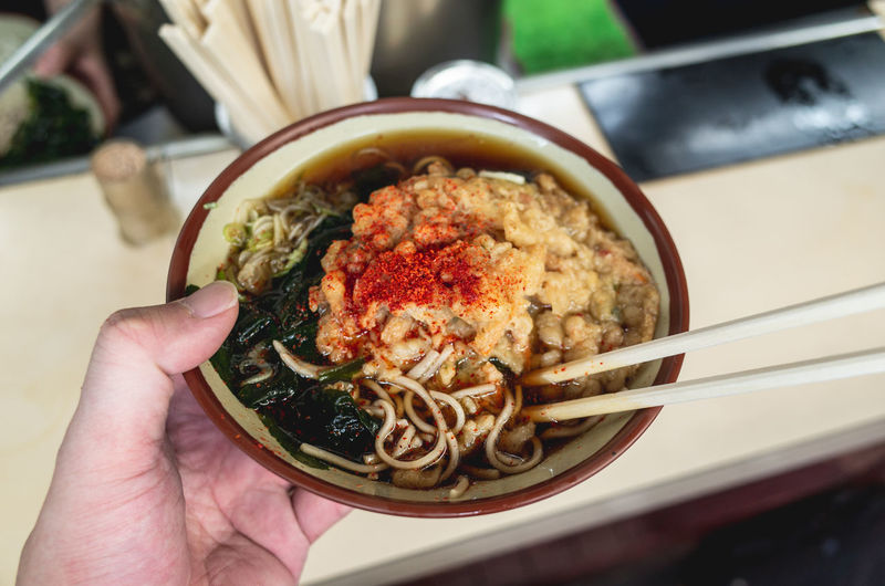 Close-Up Of Human Hand Holding Noodle Soup In Bowl