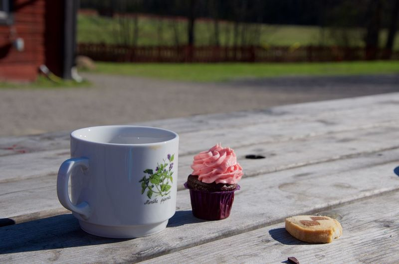 Coffee By Cupcake On Wooden Table