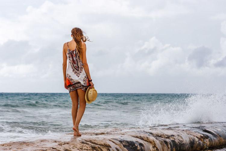 Rear view of woman walking on pier by sea