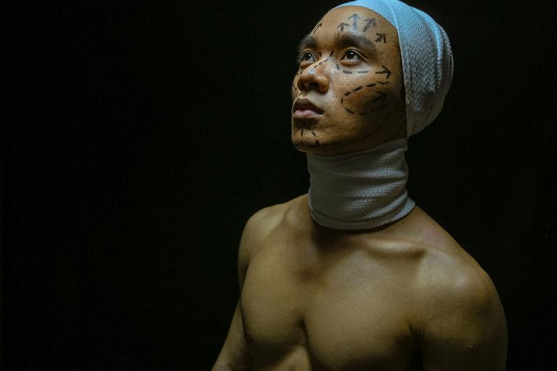 Portrait of shirtless man against black background