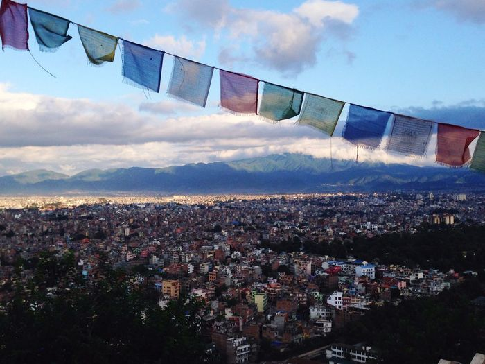Praying flags hanging over cityscape against sky