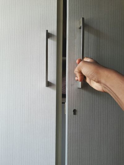 Cropped Hand Of Person Opening Cabinet Door
