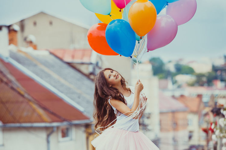 Portrait of smiling teenage girl holding balloons outdoors