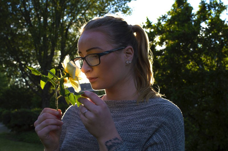 Woman Smelling Rose While Standing In Backyard