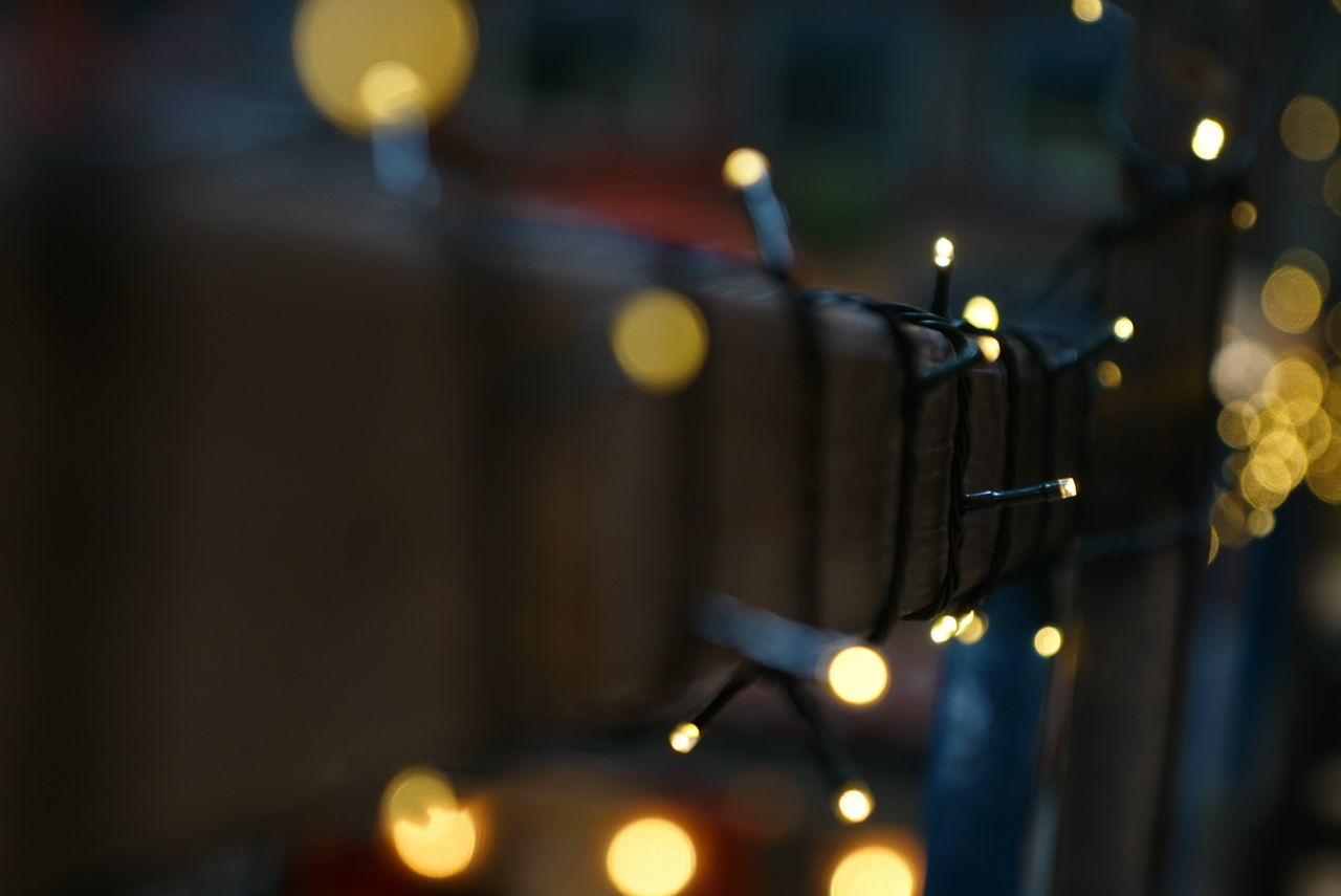 CLOSE-UP OF ILLUMINATED CANDLES ON WALL