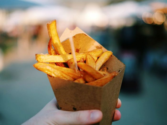 Close-Up Of Hand Holding Fries