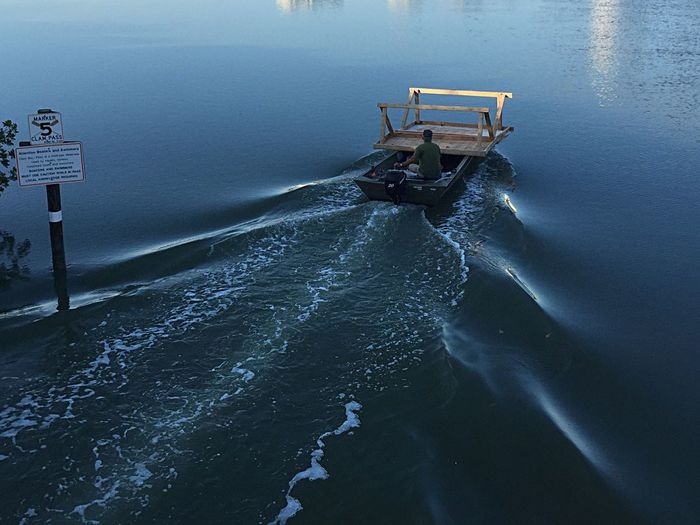 Rear view of man carrying wooden table on motorboat in water